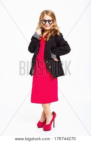 Fashion little girl in stylish mother's clothing posing holding carnival mask, smiling cheerfuly. White background.