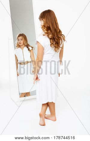 Back view of beautiful little girl in white evening dress standing in front of mirror.