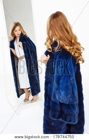 Charming little girl posing in front of mirror in mother's clothes, looking amused. Dreaming kid.