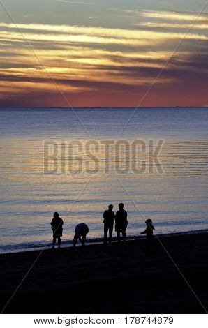 Vertical of a beautiful red/orange sunset with clouds over the blues of the North Atlantic highlights a family in silhouette at the shoreline of Race Point Beach, Provincetown, Cape Cod, Massachusetts as the last light of sunset falls in mid September.