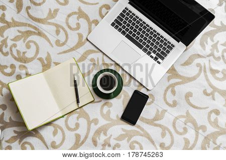 Computer, Coffee, Notebook And Pen With Cell Phone On Sofa