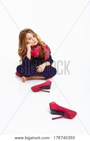 Charming girl in dress sitting on floor in lotus pose with hand on cheek.