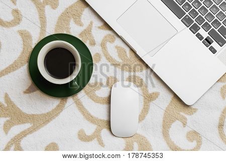 Business computer and mouse with coffee on sofa