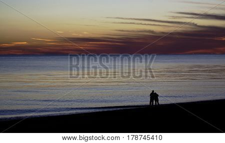 Wide view of a beautiful red/orange sunset with clouds over the blues of the North Atlantic highlights two people hugging in silhouette at the shoreline of Race Point Beach, Provincetown, Cape Cod, Massachusetts as the last light of sunset falls