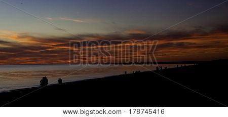Panoramic of a brilliant red sunset with clouds over the North Atlantic highlights many people in silhouette along the shoreline of Race Point Beach, Provincetown, Cape Cod, Massachusetts, as the last light of sunset falls in mid September.