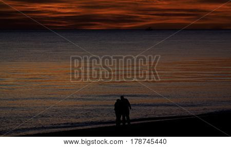 A brilliant red sunset with clouds over the North Atlantic highlights two figures in silhouette hugging at the shore of Race Point Beach, Provincetown, Cape Cod, Massachusetts as the last light of sunset falls in mid September.