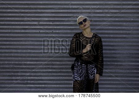 A blonde model stands against a corrugated steel wall in a tiger striped see through slip