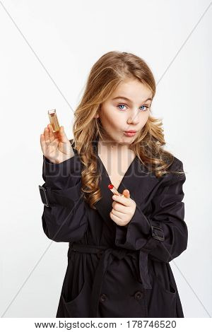Beautiful little blonde girl in trendy black trench coat opening red lipstick looking straight.
