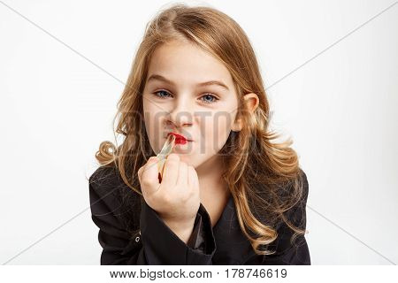 Closeup of funny little blonde girl putting on red lipstick, looking straight isolated on white.