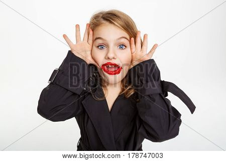 Funny little girl in trench, making faces at camera, wearing messy makeup with red lipstick.