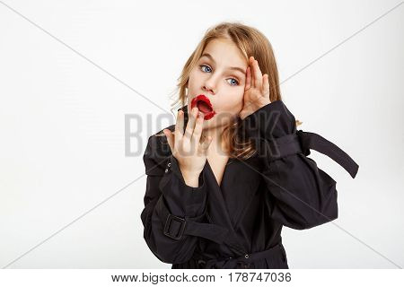 Kid with messy makeup covers mouth with left hand, right hand on face. Looking away.