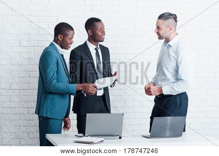Two new employees from abroad meet with leading manager for signing papers. Interracial cooperation.