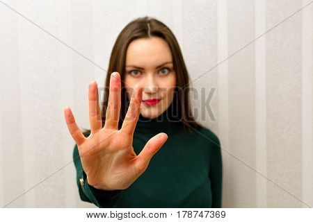 Beautiful Young Woman Making Stop Sign With Her Hand Raised Looking At Camera