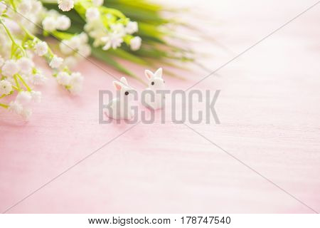 Easter Bunny Statuettes And Flowers On Wooden Background