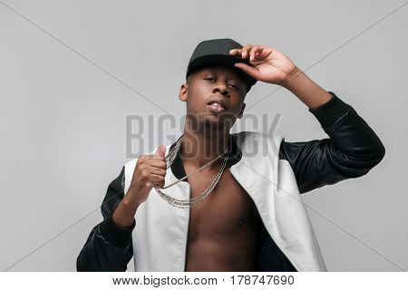 Young african american gangster man portrait on grey background with free space. Neglecting, arrogance, swagger, self-assumption. Ghetto, challenge to society, cheeky, cool, rebellious