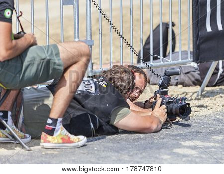 Le Mont Saint MichelFrance-July 10 2013: Image of sport photographers looking to the camera's screen while lying in the dust on the roadside during the stage 11 of the edition 100 of Le Tour de France 2013 a time trial between Avranches and Mont Saint Mic