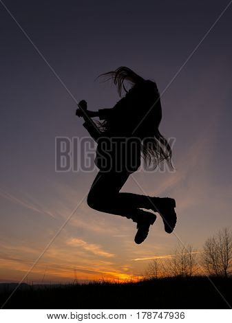 Silhouette of jumping girl with long hair during sunset.
