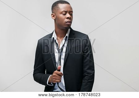 Fashion clothes, brand jackets, expensive men suits. African american guy in office dress code on grey background with free space.