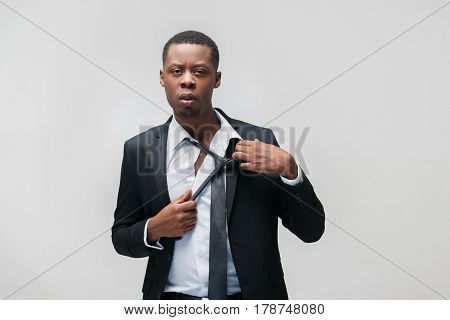 Afroamerican office employee. Tough work, problems, pressing staff, inability to rest. Grey background with copy space.