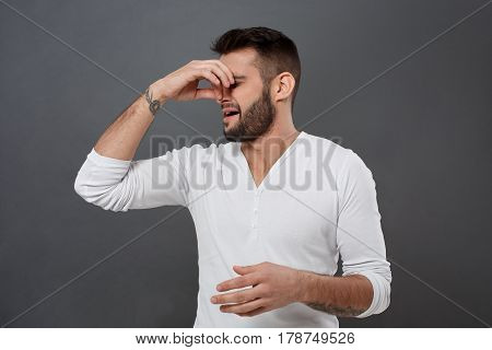 Young handsome man pinches his nose because of bad smell over grey background. Copy space.