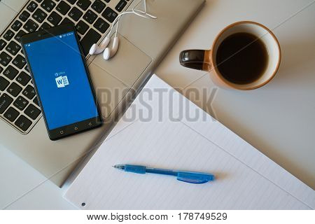Nitra, Slovakia, march 28, 2017: Microsoft office word application in a mobile phone screen. Workplace with a laptop, an earphones, notepad and coffee.