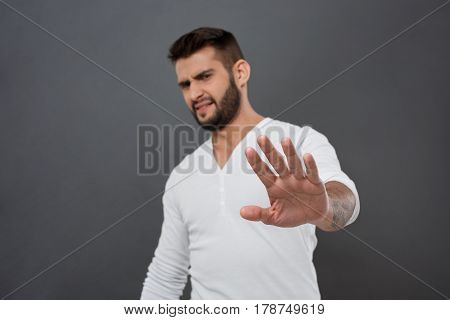 Displeased young handsome man refusing, stretching hand to camera over grey background. Copy space.