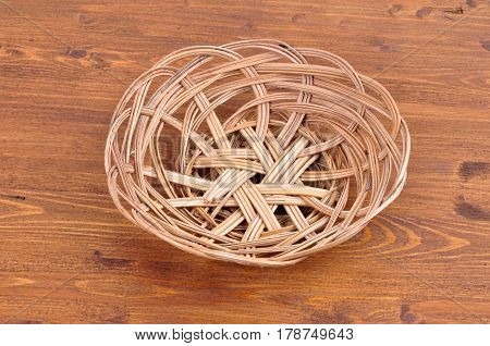 Empty wicker basket  on wooden table background. View from above