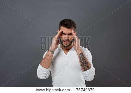 Young handsome man have headache over grey background. Copy space.