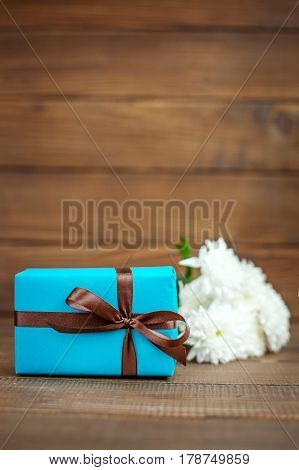 Wooden background with gift and white flowers. The concept of Mother's Day birthday March 8.