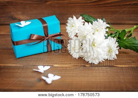 Wooden background with gift box and flowers for congratulations. The concept of Mother's Day birthday March 8.