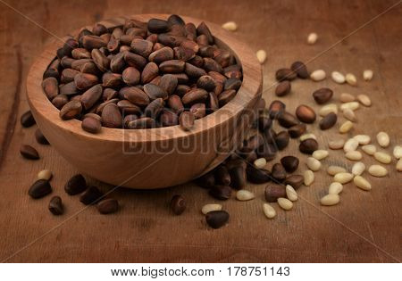 Wooden bowl of pine nuts on old wood surface