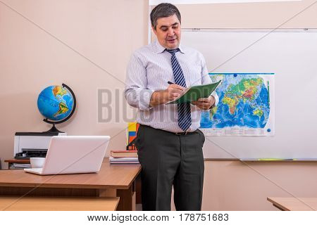 The teacher checks the presence of students in the lesson. He holds a class magazine and a pen in his hands. He looks at the papers.