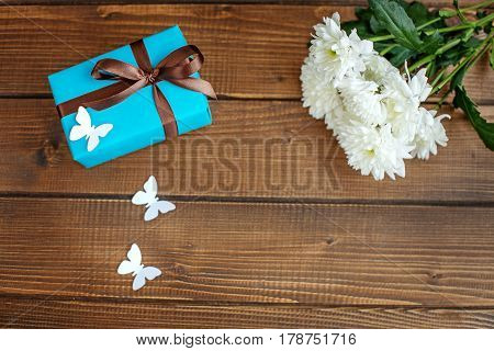 Wooden background with a gift and flowers and butterflies. Top view. The concept of Mother's Day birthday March 8.