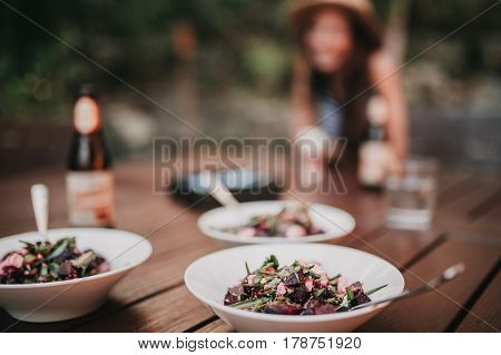 Three dishes of salad in a table, with a girl in the background.