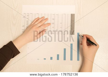 Woman Working With Graphs And Charts. In The Frame Just Hands And Paper.