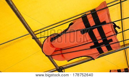 Orange Life Jacket Or Life Vest Hanging On The Roof Boat. Boat Capsized Concept.