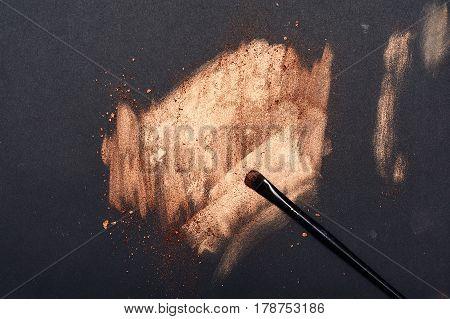 Make-up Artist's Brush on golden smeared black Surface
