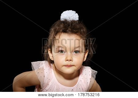 Portrait of 3 year old little girl with pink dress, gazing in camera, looks suspicious on black background