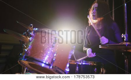 Teen rock music - sensual girl with flowing hair percussion drummer performing with drums, close up