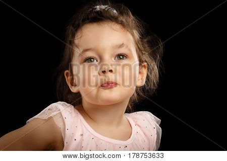 Close-up Portrait of 3 year old little girl with pink dress, send kiss on black background
