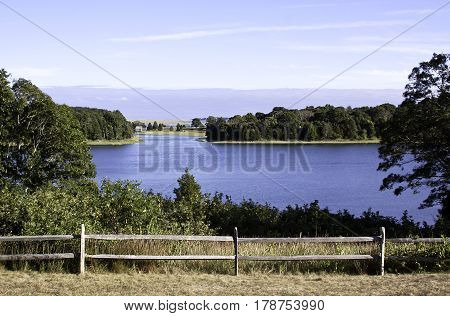 Wide view of the landscape and lake behind the Salt Pond Visitor Center in Eastham, Cape Cod, Massachusetts an old wooden fence and foliage in bottom of frame on a bright sunny day with blue skies and clouds in mid September.