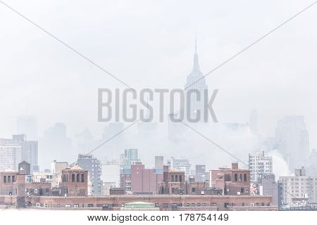 New York City, United States of America - March 24: Misty Manhattan Dimond Reef skyline with Empire State Building and skyscrapers seen from Brooklyn Bridge on March 24, 2015.