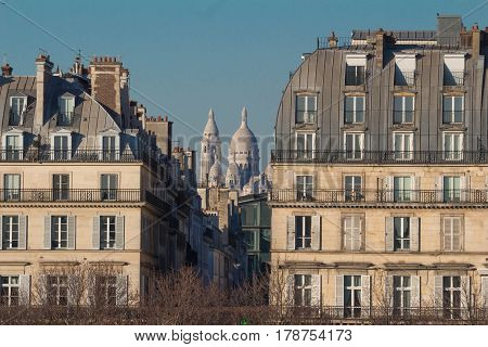 The Sacre-Coeur basilica seen between two Haussman-style buildings Paris France.
