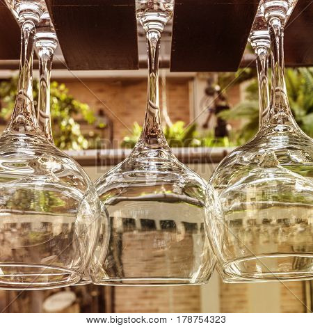 A square photo of a row of wine glasses, hanging on a rack on a restaurant terrace. Selective focus, slightly toned image