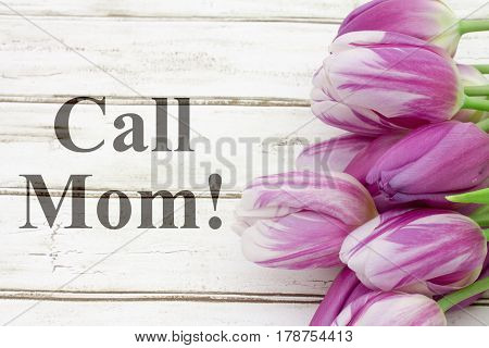 Reminder to call your mother A bouquet of purple tulips on weathered wood with text Call Mom