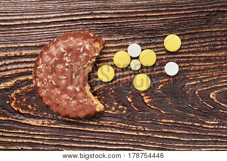 Cookie and pills on wood. Triumph over diabetes.