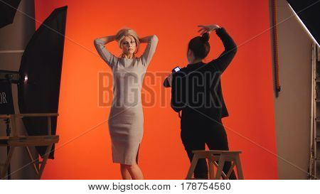 Adorable blonde girl posing for photographer - fashion backstage, red background