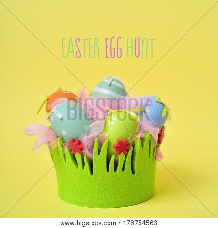 the text text easter egg hunt and a pile of different decorated easter eggs and pink feathers in a basket decorated as grass on a yellow background