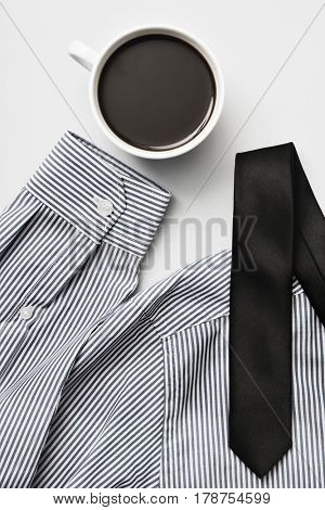 high-angle shot of a cup of coffee, a black necktie and a striped shirt on a white background