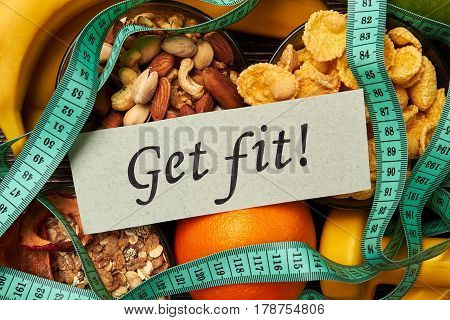 Cereals, nuts and fruits. Dumbbells and card. Get fit and be happy.